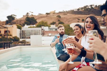Odkryty strzał szczęśliwy grupy młodych ludzi siedzi na brzegu basenu wina do picia. Wielorasowe znajomych korzystających i opiekania napojów podczas imprezy na dachu.