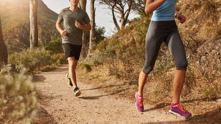 Cropped shot of two young people running on mountain trail.  Young man and women trail running on a mountain path. Stock Photo