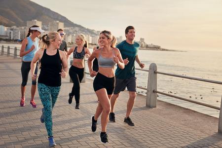 Portret młodych biegaczy korzystających z treningu na ścieżce nadmorskiej wzdłuż linii brzegowej. Prowadzenie grupy Klub wzdłuż nadmorskiej promenady. Zdjęcie Seryjne
