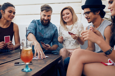 Groep vrienden ontspannen en speelkaarten samen. Jongeren opknoping samen rond de tafel tijdens een partij spelen van een spelletje kaarten. Stockfoto