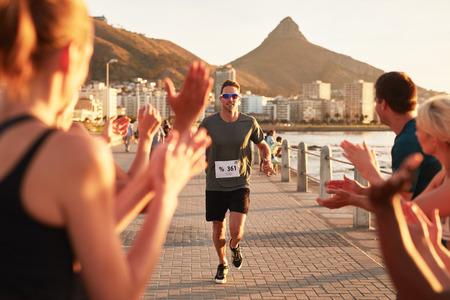 Jonge mannelijke atleet wordt toegejuicht door de supporters als hij de finish van een loopwedstrijd bereikt. Jonge mensen aan te moedigen ras lopers buiten in de stad.