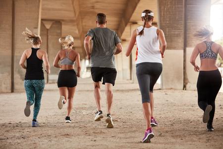 Achter portret van de groep van jonge mensen in de sport kleding die onder een brug. Runners trainen samen in de ochtend.