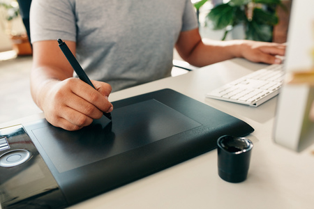 Graphic designer using digital tablet and desktop computer in the office. Close-up of designers hand working with pen. Stock Photo