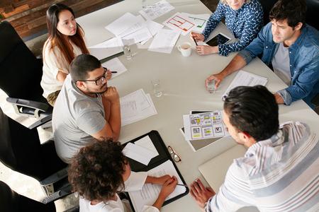 Punto di vista dell'angolo alto del gruppo creativo che si siede intorno alla tavola che discute le idee di affari. Squadra della corsa mista di professionisti creativi che si incontrano nella sala conferenze.