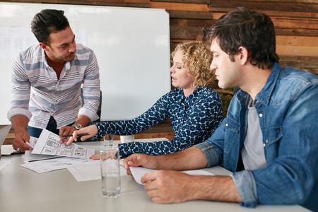 若い男性と女性は、オフィスで会議中にテーブルでの議論を行います。創造的なチームが新たなビジネス戦略を計画します。