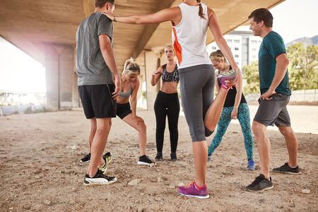 Grupo de jóvenes amigos se extiende debajo de un puente después de correr por la mañana. Grupo corriente de club de tomar un descanso de la formación. Foto de archivo