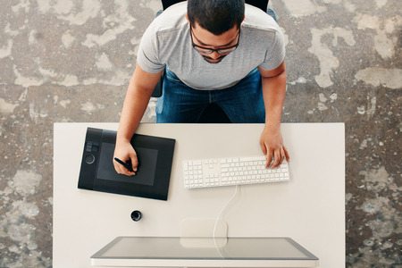 digitizer: Top view of a male graphic designer using digital graphics tablet and desktop in the office. Editor sitting at his desk drawing on digitizer with stylus.