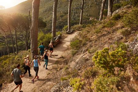 젊은 사람들의 그룹은 산길에서 실행 흔적. 아름다운 자연 속에서 운동을 주자.