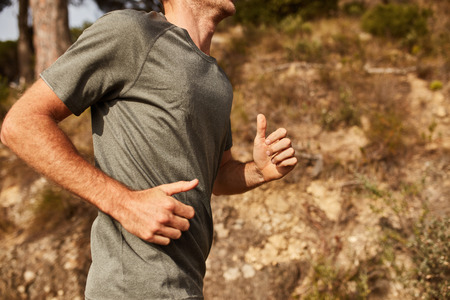 cropped: Cropped shot of young man running outdoors. Trail running workout. Stock Photo