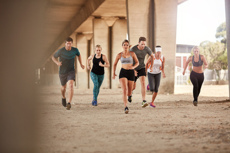 people together: Portrait of group of runners in fitness clothing running under a bridge. Young men and women doing running work out together. Stock Photo