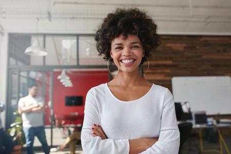 Jovem mulher de sorriso que está com seus braços cruzados e olhando a câmera. Ela está em um escritório moderno com seus colegas em segundo plano.