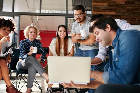 Tým kreativních lidí při pohledu na kolegu ukazuje plán projektu na svém notebooku. Různorodá skupina mladých lidí s setkání v kanceláři. Jsou diskutovat o novém projektu.