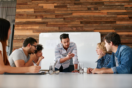 Мозговой штурм в конференц-зале творческого офиса. Молодые творческие люди, сидящие за столом и обсуждают новые проекты. Фото со стока