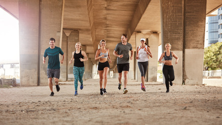 jogging: Portrait of group of runners from running club under a bridge. Young men and women jogging together. Stock Photo