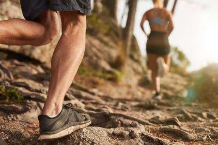 rocky road: Closeup of male feet run through rocky terrain. Cross country running with focus on runners legs. Stock Photo