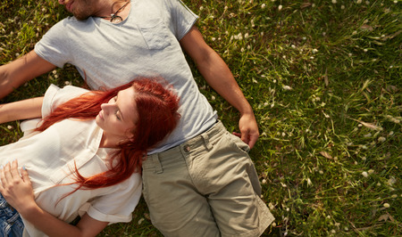 lying on back: Young woman lying on the lawn with her boyfriend. Overhead view of young couple relaxing on the grass, with copy space.