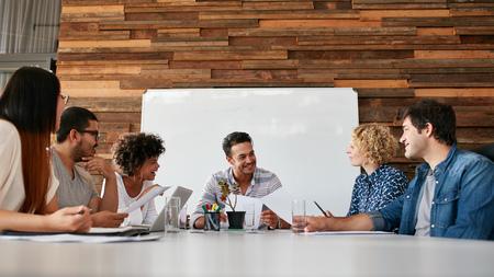 Groep gelukkige jonge mensen uit het bedrijfsleven bijeen in de vergaderzaal. Team van creatieve professionals bespreken nieuw project.