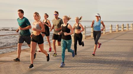 海沿いにビーチ ボードウォークに沿って実行している若者の肖像画。フィットの若い男性と女性は、海辺で屋外トレーニングを実行しています。
