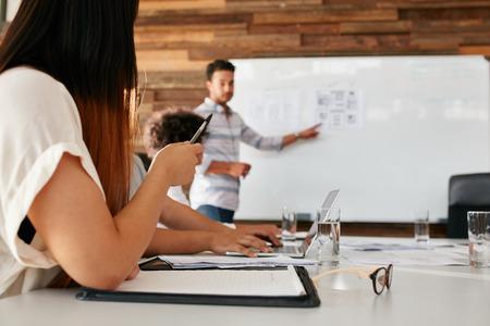 Imagem do close up de uma jovem sentada em uma reunião na sala de reuniões com o homem que dá a apresentação no fundo. Foco nas mãos do executivo fêmea. Banco de Imagens