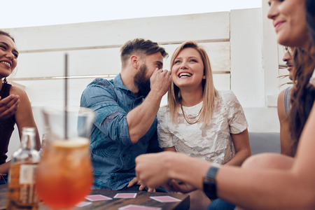 Young people sitting together in a party. Man whispering something in womans ears. Sharing a secret. Stock Photo