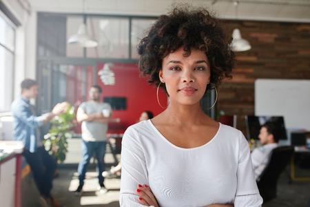 카메라를보고 바쁜 창조적 인 사무실에 서있는 여자의 초상화. 디자인 스튜디오에서 매력적인 여성 창조적 인 전문.