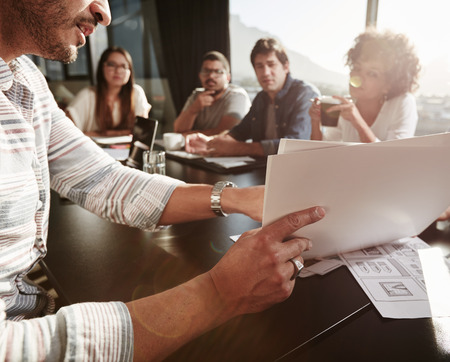 Крупным планом руки молодой человек, объясняя бизнес-план с коллегами. Творческие люди, собравшиеся в конференц-зале. Фото со стока