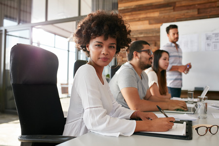 black professional: Portrait of confident businesswoman sitting at a business presentation with colleagues in boardroom. African woman with coworkers in conference room.