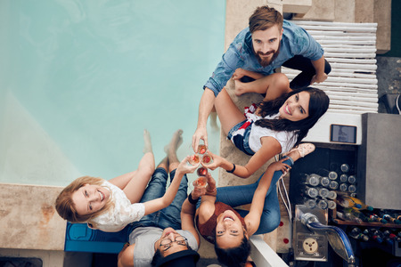Overhead view of group of friends toasting at party by a swimming pool and looking up at camera smiling. Multiracial young people sitting by the pool having wine during party.