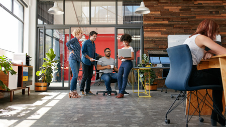Retrato de um grupo de pessoas criativas que têm uma reunião com um laptop em um escritório moderno. Executivos que têm relaxado conversa durante o novo projeto. Banco de Imagens
