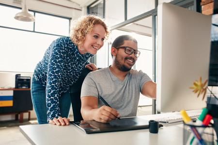 Dos jóvenes diseñadores de hombres y mujeres trabajando juntos, con el hombre edición de obras de arte que usa la tableta gráfica y un lápiz óptico. Las personas creativas de coworking en un nuevo proyecto en la oficina.