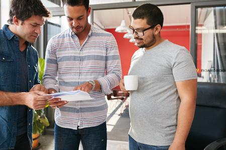 obreros trabajando: Grupo de profesionales creativos j�venes que tienen una reuni�n en la oficina, pasando por algunos documentos juntos. equipo creativo de tres hombres j�venes que trabajan en el nuevo proyecto. Foto de archivo
