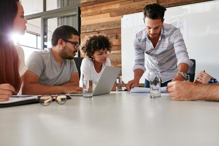 lider: Hombre que presenta la joven es ideas a colegas durante la reunión en la sala de conferencias. Líder muestra plan de negocio a colegas durante una reunión.