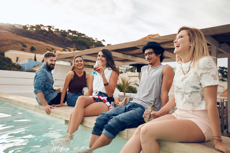 Young people drinking cocktails by the pool during party. Young friends laughing while sitting by a swimming pool. Men and women partying outdoors.