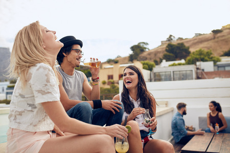 飲み物を持つと楽しんで幸せな若者ながら座っていると、バック グラウンドで互いに話している彼らの友人。若い男性と女性の屋上パーティーしま