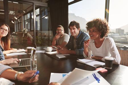 オフィスで会議中に新経営計画を論議している若い人々 のチーム。Net のプロジェクトのオフィスでデザイナーの混血チーム。