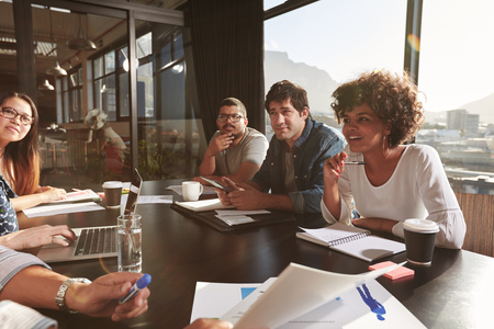 Zespół młodych ludzi omawiania nowego planu biznesu podczas spotkania w biurze. Mieszane wyścigu zespół projektantów omawianie projektów netto w biurze.