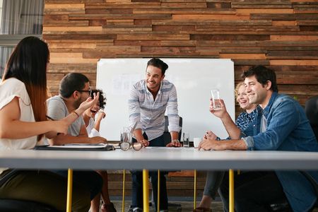 advertising woman: Group of happy young people having a business meeting. Creative people sitting at table in boardroom with man explaining business strategy. Stock Photo