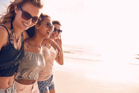 Gruppe von schönen jungen Frauen auf einem Strand entlang. Drei Freunde am Strand spazieren und Lachen an einem Sommertag, Urlaub genießen.