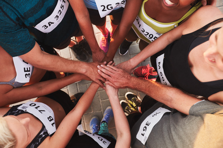 High angle portrait of a sports team standing in a circle with their hands stacked. Team of runners with hands together after competition.