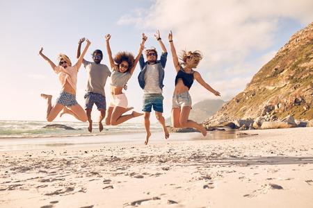Grupp vänner tillsammans på stranden att ha roligt. Lyckliga ungdomar hoppar på stranden. Grupp vänner njuter sommarlovet på en strand.