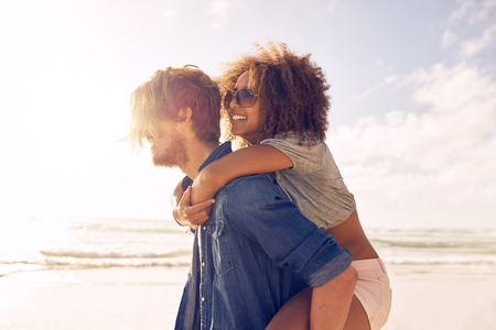 carrying: Side view portrait of young man carrying his girlfriend on his back at the beach. Boyfriends giving piggyback ride to his beautiful girlfriend at seashore.