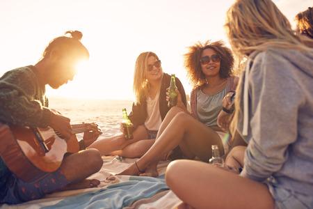 Groep jonge mensen zitten op het strand bij elkaar, terwijl de jonge man gitaar spelen. Groep vrienden feesten op het strand bij zonsondergang.