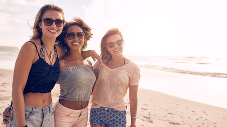 looking to camera: Portrait of three young female friends standing together on the sea shore looking at camera and smiling. Multiracial group of young women posing on a beach with copy space.