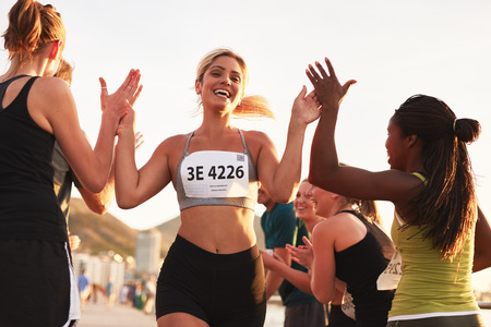 on  line: Multi ethnic group of young adults cheering and high fiving a female athlete crossing finish line. Sportswoman giving high five to her team after finishing the race. Stock Photo