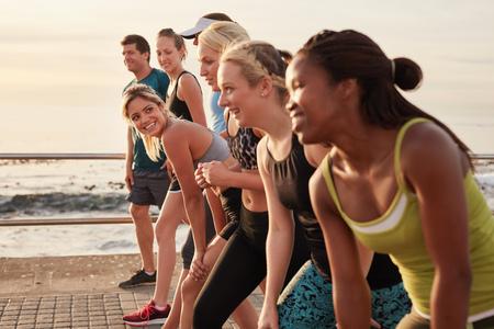 Grupa młodych sportowców w pozycji startowej, koncentrują się na kobiety. Fit młodych ludzi przygotowujących się do wyścigu wzdłuż morza. Zdjęcie Seryjne