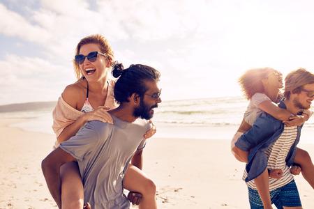 Gelukkige jonge mensen die op de rug rit naar vrouwen op het strand. Diverse groep jonge mensen met plezier op het strand en meeliften. Stockfoto