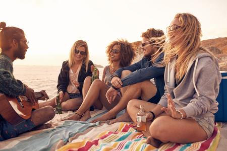 음악과 음료와 함께 해변 파티를 즐기는 젊은 친구. 해변에 앉아 맥주를 마시는 그의 친구와 함께 기타를 연주하는 젊은 남자.
