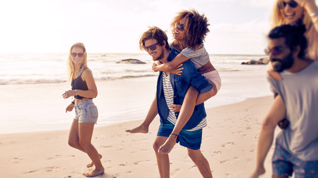 Two happy young men giving their girlfriends piggyback rides at the beach. Group of friends enjoying beach holidays. 版權商用圖片