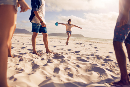 Low angle shot of young woman running on the beach with a ball with her friends standing in front. Group of friends enjoying holiday on the beach. Stock Photo