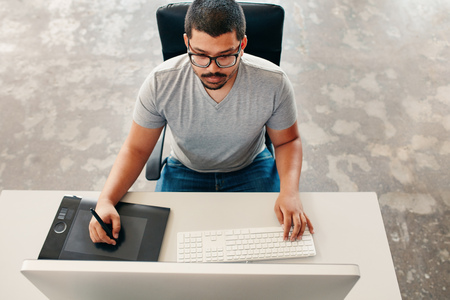 design drawing: High angle image of young man using a stylus and tablet while working on his computer. Graphic designer working at his desk.